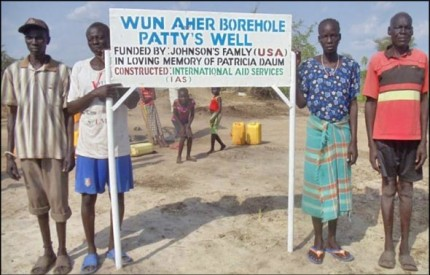 The sign post for Patty's Well is erected in Malual Chat along with the newly drilled well.